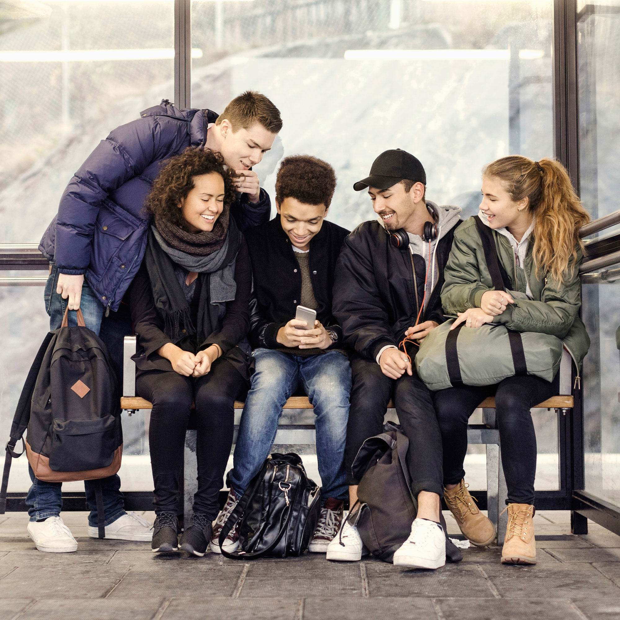Youths waiting at bus stop in wintertime.